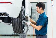 Asian mechanic checking and repairing the car wheels in maintain